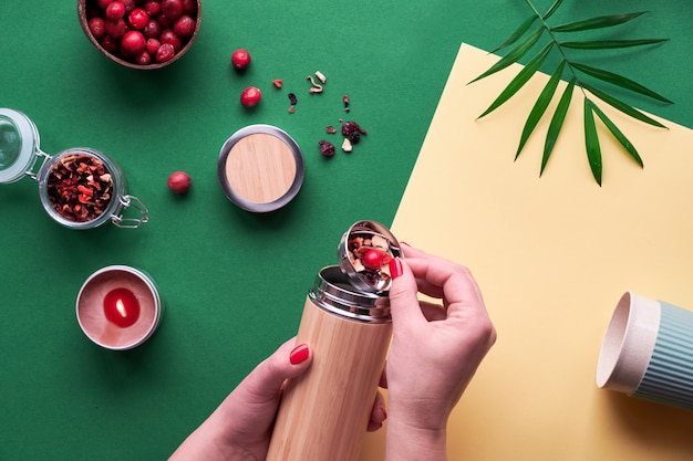Zero waste tea to go, making herbal infusion in eco friendly insulated bamboo steel flask with herbal mixture and fresh cranberry.