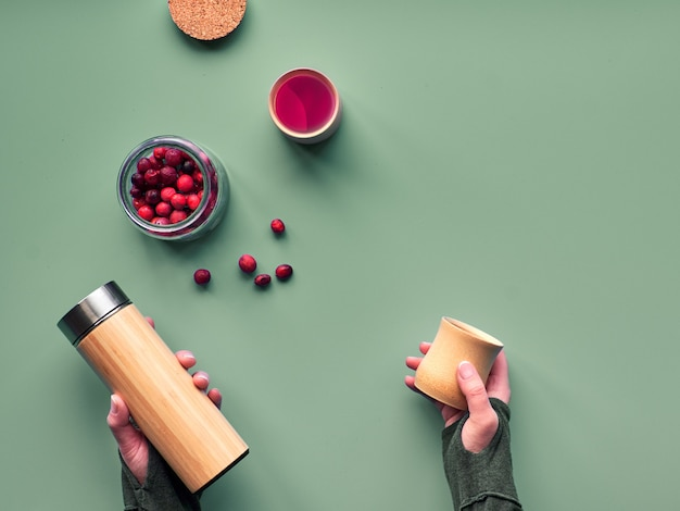 Zero waste tea in travel flask. making herbal infusion in eco friendly insulated bamboo flask with fresh cranberry. trendy flat lay. hands holding the flask and natural bamboo cup.