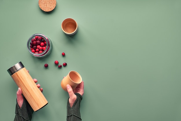 Zero waste tea in travel flask. making herbal infusion in eco friendly insulated bamboo flask with fresh cranberry. trendy flat lay with text space. hands holding the flask and natural bamboo cup.