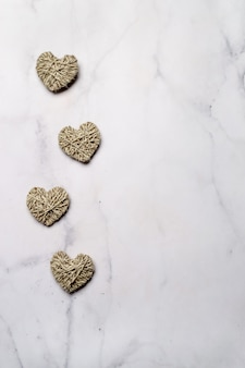 Zero waste, valentine's day eco-friendly concept. hearts with yarn on white marble background. copy space for text or design. top view or flat lay vertical.