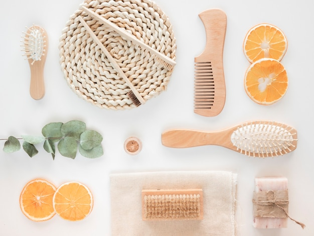 Zero waste wooden bath accessories concept. top view craft soap, orange wedges and eucalyptus branch over white background