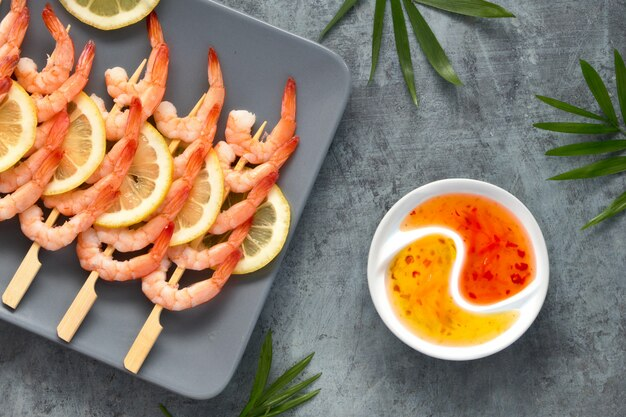 Zesty lemon and garlic prawns on wooden sticks, flat lay on dark