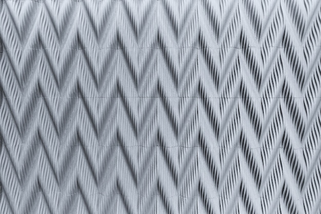 Zigzag decorative gray concrete tile relief on the wall. convex pattern