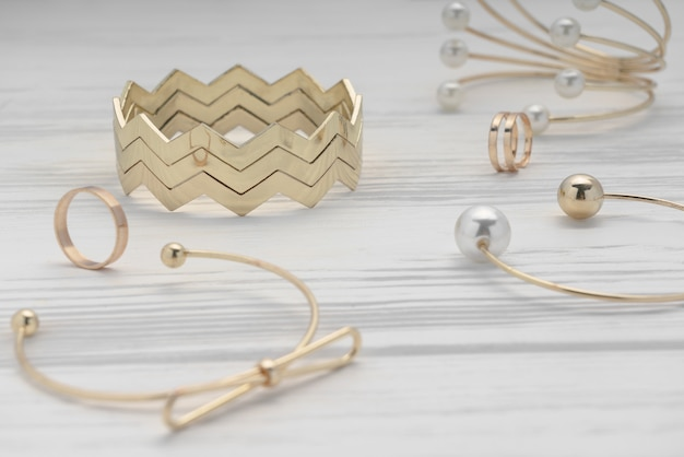 Zigzag shape golden bracelet between golden girl accessories on wooden table