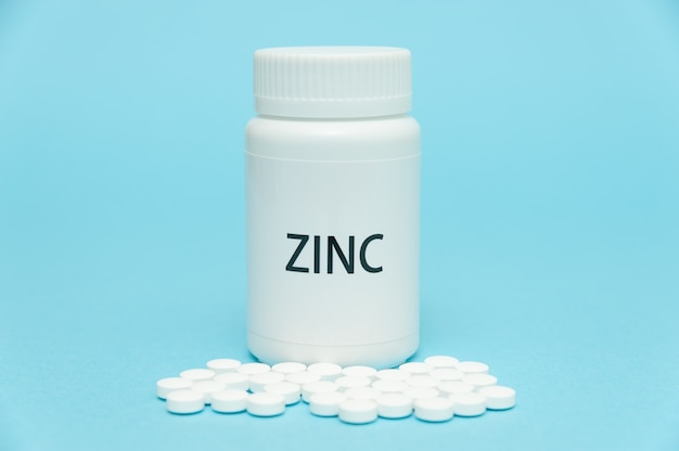 散在する丸薬が付いている白いびんの包装の亜鉛。栄養補助食品。