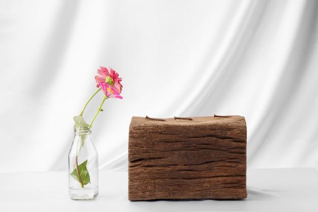 우아한 패브릭 배경에 제품을 배치하기 위해 목재 옆 병에 백일초 꽃
