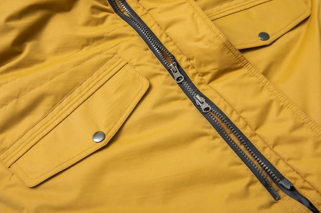 Молния и накладные карманы на водостойкой желтой куртке для весны и осени.