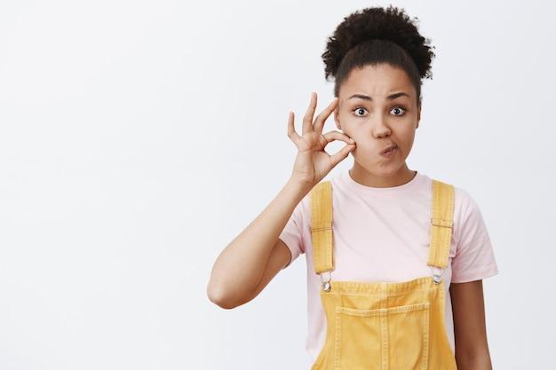 내 입을 영원히 닫아 비밀 금고. 매력적인 심각한 아프리카 계 미국인 여자 약속을 만들고, 보이지 않는 지퍼로 입술을 닫고, 입을 오른쪽으로 삐죽이고 뺨 근처에 손가락을 잡고의 초상화
