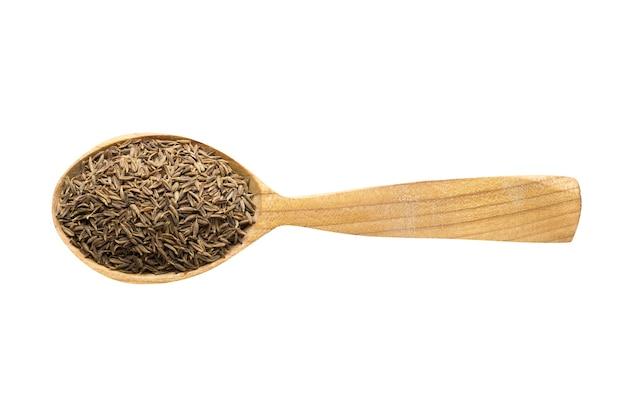 Зира черная для добавления в пищу. специи в деревянной ложке, изолированные на белом. приправа к вкусной еде.