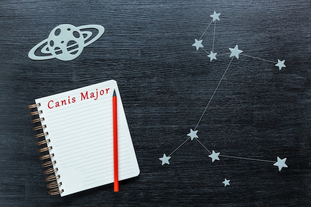 Zodiacal star, constellations canis major on a black background with a notepad and pencil.