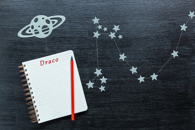 Zodiacal star, constellations draco on a black background with a notepad and pencil.