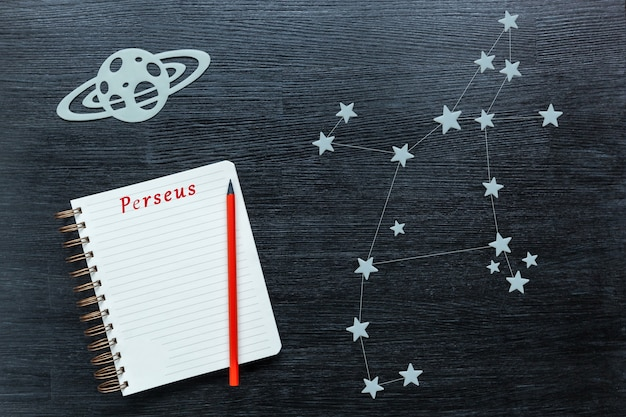 Zodiacal star, constellations perseus on a black background with a notepad and pencil.