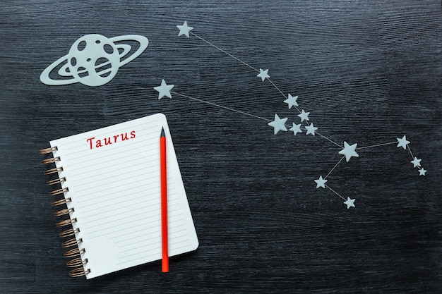 Zodiacal star, constellations taurus on a black background with a notepad and pencil.