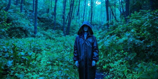 ゾンビの黙示録。雨のコートを着た男は、濡れた森の背景に立ち戻ります。森に雨が降ります。暗いレインコート。自然。インフルエンザウイルスの流行。青い肌の森のゾンビ男