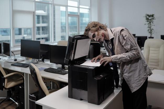 Зомби-бизнесмен, стоящий у ксерокопии и копирующий документы в офисе