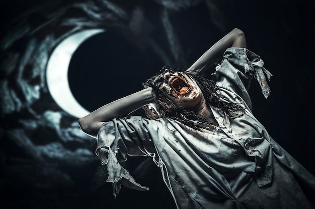 Zombie girl against the moon. scary. halloween.