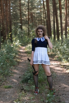 A zombie girl with an axe in her hands in a gloomy forest.halloween costume