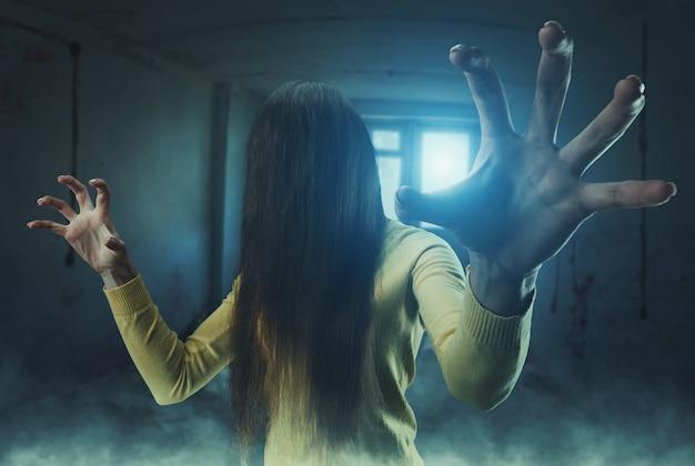 버려진 건물에서 그녀의 얼굴에 긴 머리를 가진 좀비 소녀