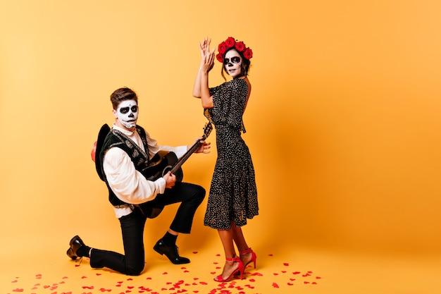 Zombie guy singing serenade for his dead bride. indoor portrait of spooky couple celebrating halloween together.