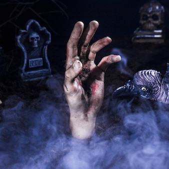 Zombie hand and creepy raven at halloween graveyard