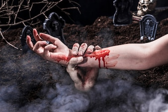 Zombie hand holding bloody woman arm at Halloween graveyard