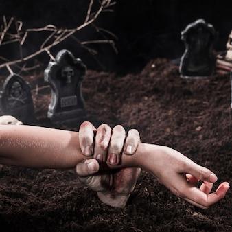 Zombie hand holdingperson arm at halloween graveyard