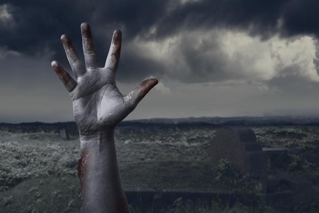 Рука зомби с кровью и раной поднята с кладбища