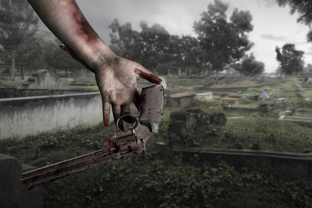 Zombie hands with wound drop the gun on the cemetery