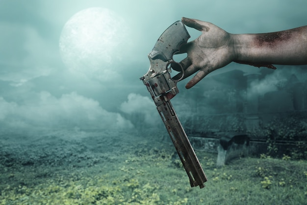 Zombie hands with wound drop the gun with the night scene background
