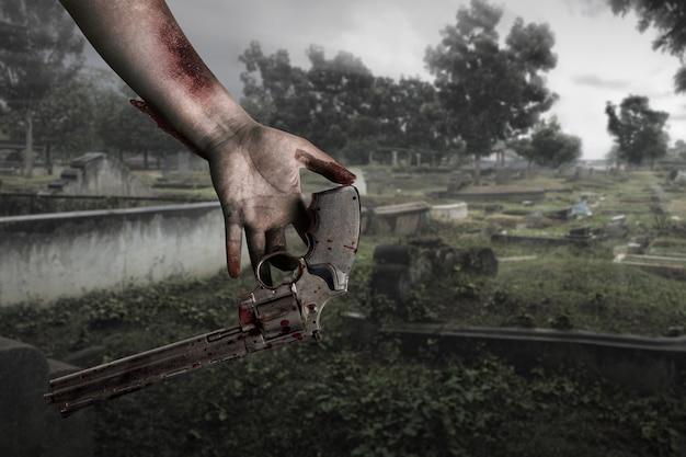 Руки зомби с раной бросают пистолет на кладбище