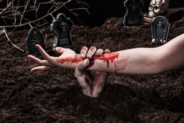 Zombie holding bloody female hand at halloween graveyard