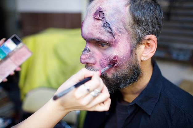 ハロウィーンのコンセプトを適用するゾンビ男性メイク。ブラシでメイクし、肌と血の顔をペイントします