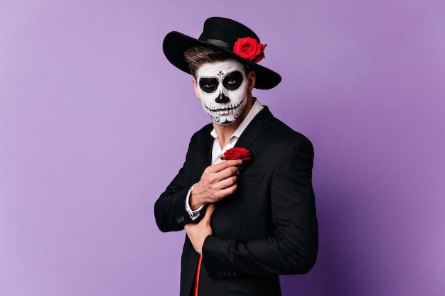 Uomo zombie in cappello nero in posa su sfondo viola. tiro al coperto del modello maschile in sombrero che celebra halloween.