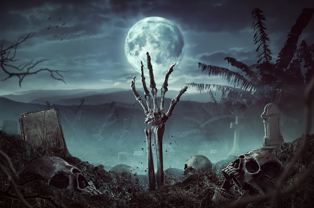 Рука скелета зомби поднимается в темную ночь хэллоуина.