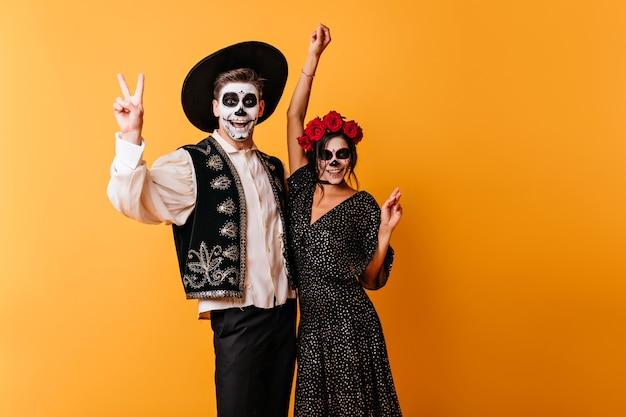 Зомби в мексиканских нарядах, выражающие счастье. очаровательная молодая женщина празднует хэллоуин с другом.