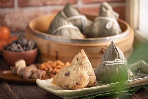 Zongzi chinese rice dumpling zongzi in a steamer on wooden table for dragon boat festival