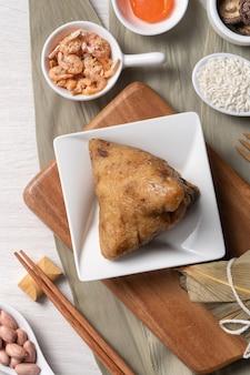 ちまき。木製のテーブルの背景の上面図上のドラゴンボートduanwuフェスティバルのためのおいしい伝統的な餃子料理。