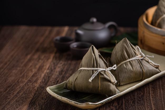 ちまき。暗い木製のテーブルの背景に中国の伝統的なドラゴンボートフェスティバル(duanwuフェスティバル)のちまき。