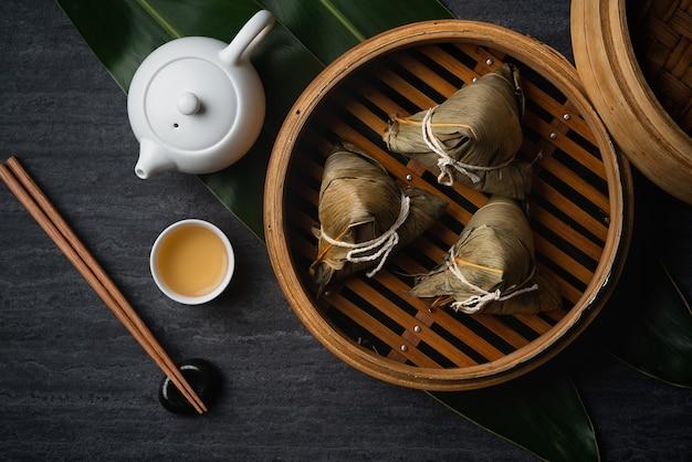 어두운 검은 색 슬레이트 배경 위에 중국 전통 용 보트 축제 (duanwu 축제)를위한 zongzi 쌀 만두 평면도