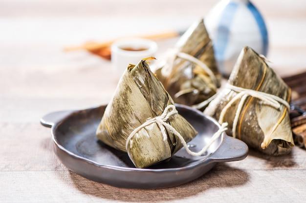 ドラゴンボートフェスティバルの木製テーブルにお茶を入れたzongzi(餃子)