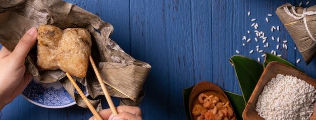 青い木製のテーブルの背景に中国の伝統的なドラゴン ボート フェスティバル (duanwu フェスティバル) の食材のトップ ビューで zongzi 米餃子 Premium写真