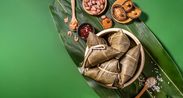 Zongzi, steamed rice dumplings on green table background, food in dragon boat festival duanwu concept, close up, copy space, top view, flat lay