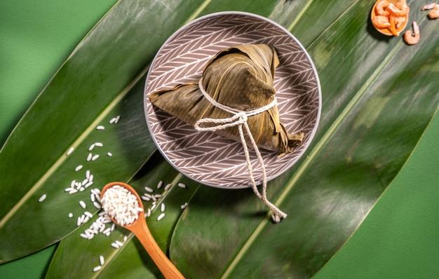 Zongzi, 녹색 테이블 배경에 찐 쌀 만두, 드래곤 보트 축제 duanwu 개념의 음식, 가까이, 복사 공간, 평면도, 평면 누워