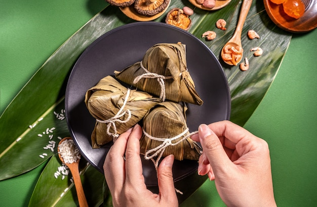 Zongzi, woman eating steamed rice dumplings on green table background, food in dragon boat festival duanwu concept, close up, copy space, top view, flat lay