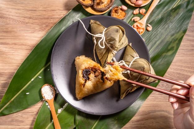 Zongzi, 나무 테이블에 찐 쌀 만두를 먹는 여자, 드래곤 보트 축제 duanwu 개념의 음식, 가까이, 복사 공간, 평면도, 평면 누워
