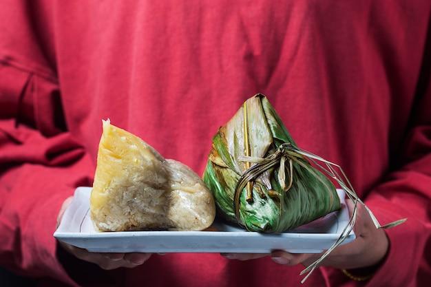 女性がドラゴンボートフェスティバルのプレゼントとして他人にzongzi(米団子)を贈っています