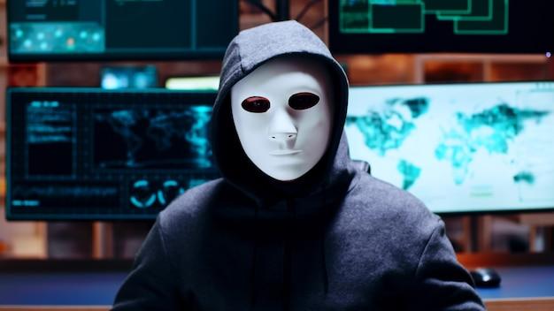 흰색 마스크를 쓰고 카메라를 바라보는 사이버 범죄자를 확대합니다.
