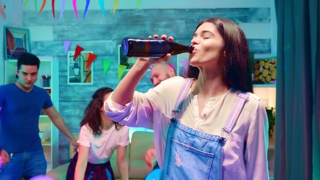 네온 불빛과 함께 야생 파티에서 병에서 맥주를 마시는 아름다운 소녀의 샷을 확대합니다. 배경에서 춤추는 사람들의 그룹