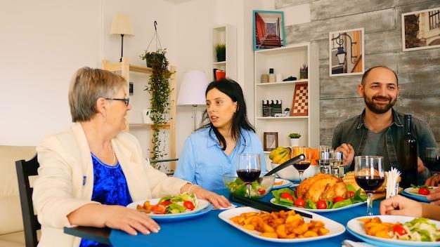 家族の夕食で60代の母親と話している美しい若い女性のショットを拡大表示します。