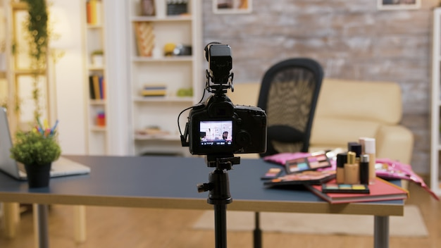 テーブルの上に化粧品とプロの録音機器がある空のインフルエンサールームのショットを拡大します。